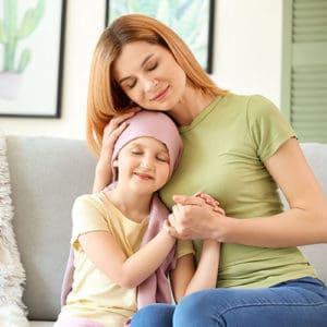 Menina paciente de câncer com a mãe em casa